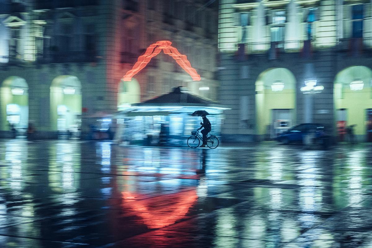uomo pedala sotto la pioggia